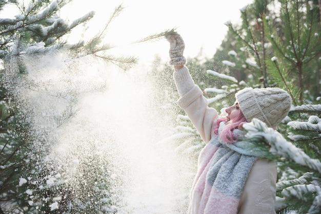 Mooi meisje met roze haar dat sneeuw van bomen blaast