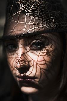 Mooi meisje met schaduwweb op gezicht