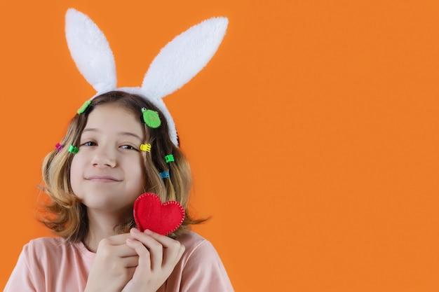Mooi meisje met schattig gezicht en konijnenoren op haar hoofd met gebreid hart in haar handen. paasvakantie
