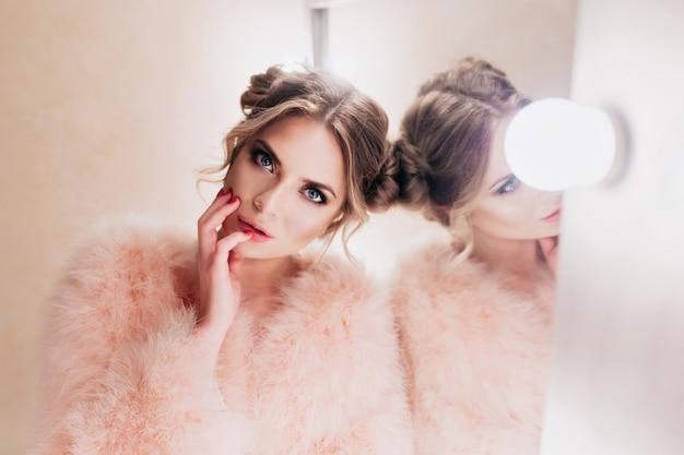 Mooi meisje met schattig kapsel aanraken van haar gezicht tijdens het wachten op fotoshoot in de kleedkamer. schitterende gekrulde jonge vrouw in roze jasje op zoek met interesse poseren naast make-up spiegel