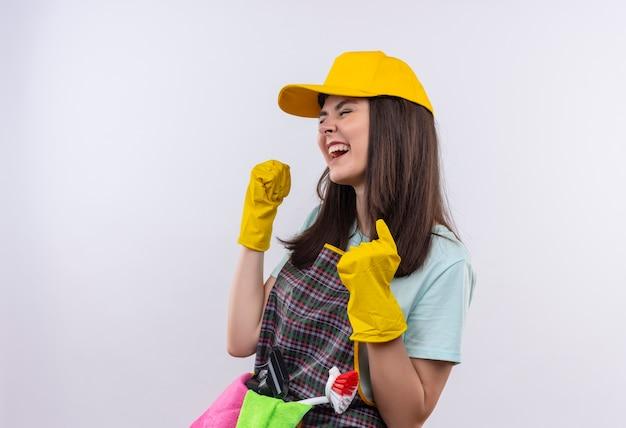 Mooi meisje met schort, pet en rubberen handschoenen gekke gelukkige gebalde vuisten verheugend haar succes