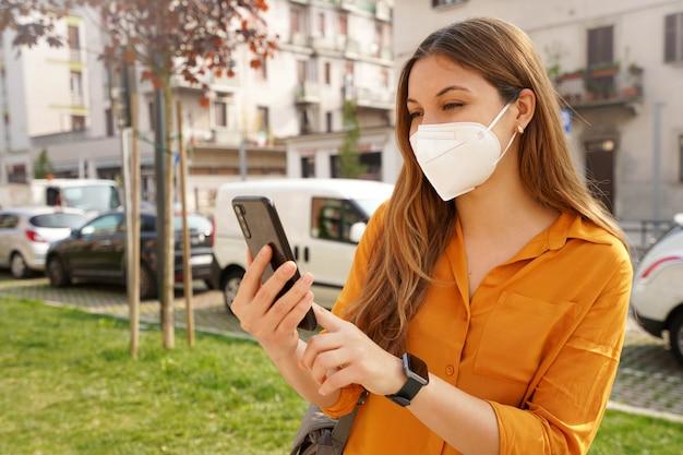 Mooi meisje met smartwatch met kn95 ffp2-gezichtsmasker met mobiele telefoon in stadsstraat in