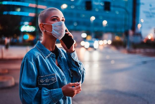 Mooi meisje met stijlvolle kleding smartphone buiten houden in de avond verlichte stad op het oppervlak