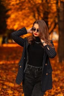 Mooi meisje met stijlvolle zonnebril in een modieus zwart pak met een blazer en een zwarte trui loopt in een herfstpark met kleurrijke herfstbladeren