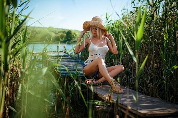 Mooi meisje met strohoed zit bij de rivier op metselwerk
