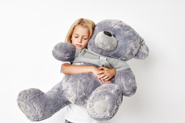 Mooi meisje met teddybeer een stuk speelgoed op een lichte achtergrond