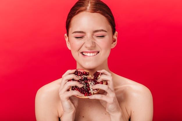 Mooi meisje met verse granaat lachen met gesloten ogen. studio shot van lachende geweldige vrouw met granaatappel op rode achtergrond.