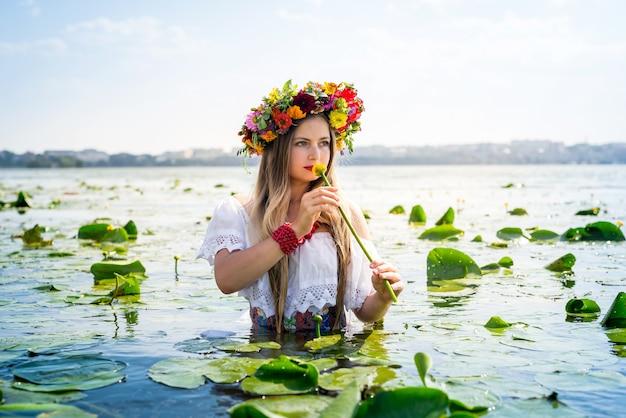 Mooi meisje met waterlelie die zich in water bevindt