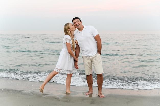 Mooi meisje met wit haar kust haar man op de wang op het strand in de buurt van de oceaan bij zonsondergang.
