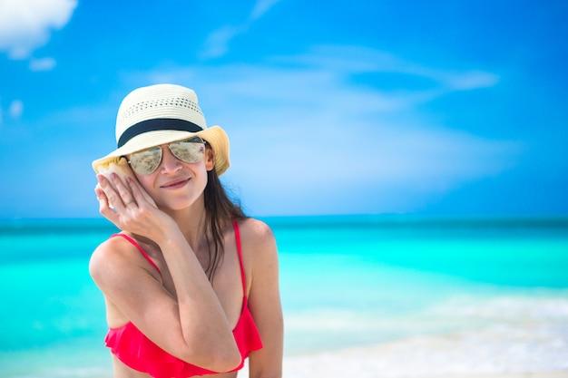 Mooi meisje met zeeschelp in handen bij tropisch strand