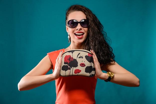 Mooi meisje met zonnebril en handtas in haar handen