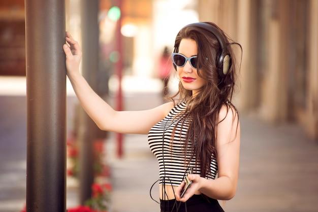 Mooi meisje met zonnebril en koptelefoon in straat