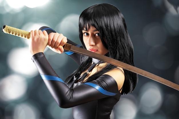 Mooi meisje met zwaard op bokehachtergrond