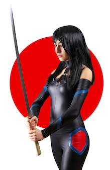 Mooi meisje met zwaard op de achtergrond van de japanse vlag. meisje poseren met een zwaard Premium Foto