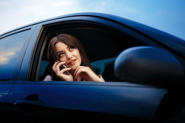 Mooi meisje model zit in de auto en gebruik de telefoon
