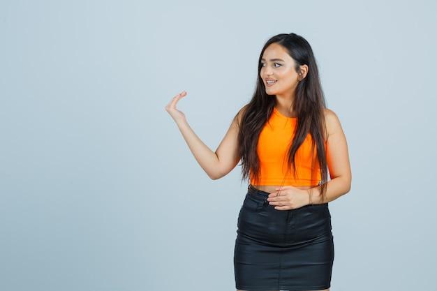 Mooi meisje nodigt uit om te komen in oranje top, rok en ziet er vriendelijk uit. vooraanzicht.