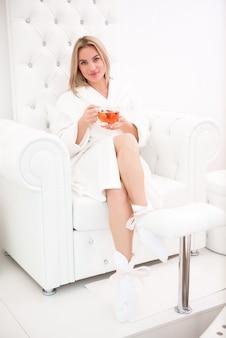 Mooi meisje ontspant in een witte badjas met een kopje thee in haar handen in de spasalone.