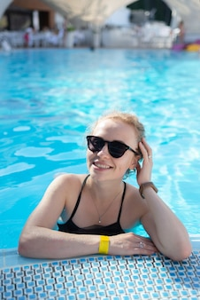 Mooi meisje ontspant in het zwembad in zonnige dag
