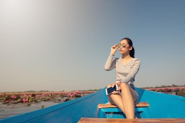 Mooi meisje op blauwe boot in roze lotus meer in de ochtend. zon bescherming.