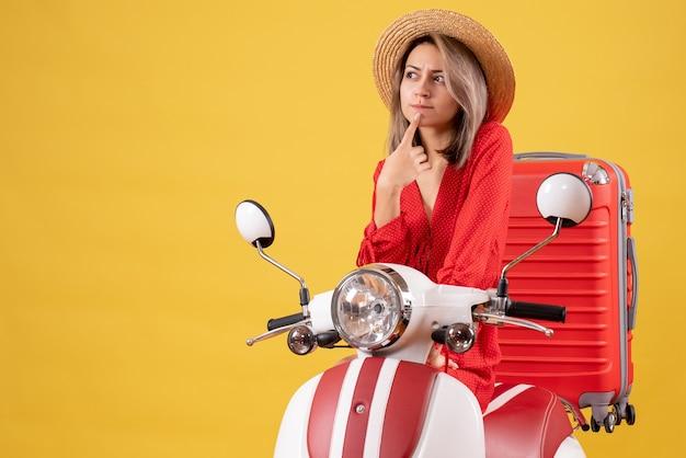 Mooi meisje op bromfiets met rode koffer die ergens aan denkt
