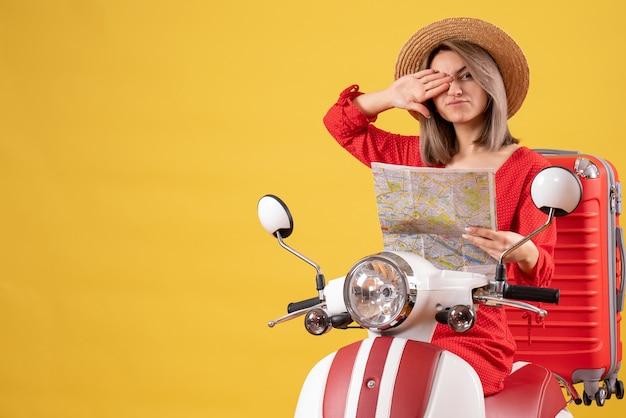 Mooi meisje op bromfiets met rode koffer met kaart die één oog met hand bedekt covering