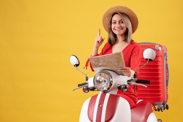 Mooi meisje op bromfiets met rode koffer met kaart wijzend met vinger omhoog