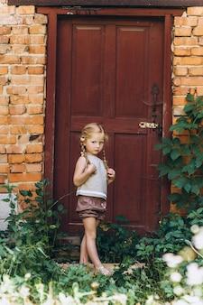 Mooi meisje op de achtergrond van een deur met haar gevlochten in twee spleten