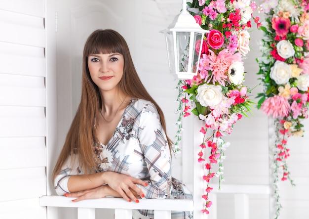 Mooi meisje op de veranda met witte lantaarn, versierde bloemen.