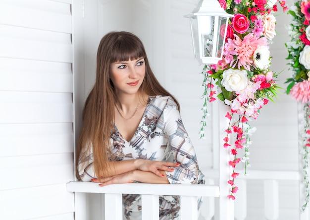 Mooi meisje op de veranda met witte lantaarn, versierde bloemen
