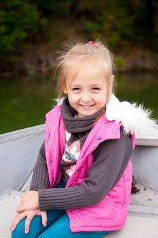 Mooi meisje op een boot op het meer