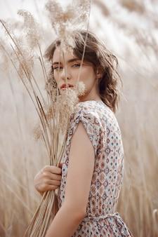 Mooi meisje op een gebied met lang gras in de herfst. kunstportret van een vrouw