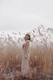 Mooi meisje op een gebied met lang gras in de herfst