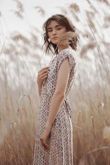 Mooi meisje op een gebied met lang gras in de herfst.