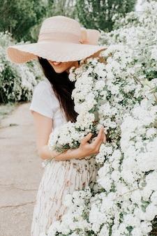 Mooi meisje op een witte achtergrond van bloemen.