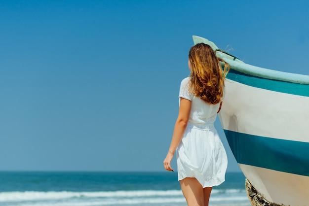 Mooi meisje op tropisch strand in de buurt van vissersboot