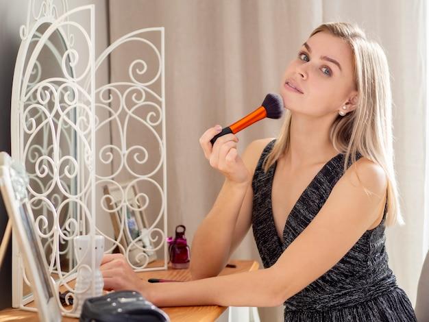 Mooi meisje op zoek op camera en cosmetische met een grote borstel toe te passen op een gezellige slaapkamer interieur.