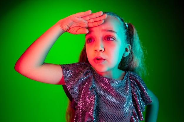 Mooi meisje op zoek verrast geïsoleerd op groene muur