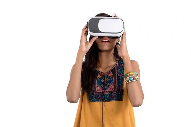 Mooi meisje op zoek via vr-apparaat. jong meisje dat de hoofdtelefoon van virtuele werkelijkheidsbeschermende brillen draagt.