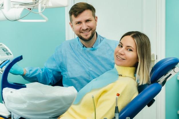 Mooi meisje patiënt toont de klas met haar hand zittend in de stoel van de tandarts.