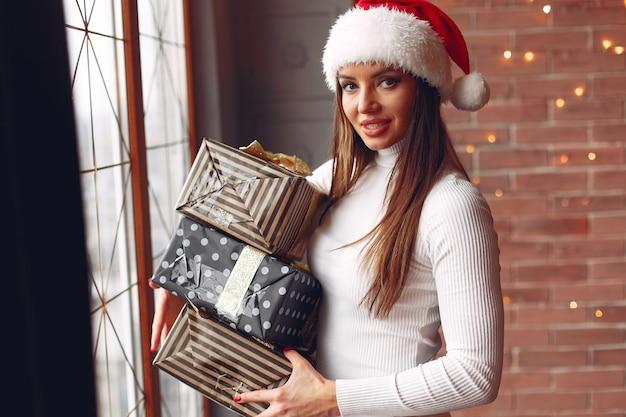 Mooi meisje permanent in de buurt van venster met cadeautjes