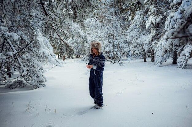 Mooi meisje permanent, in de winter in bospark, achtergrond van kerstboom sneeuw, ze rust in resort. vrije ruimte voor tekst. blauwe jumpsuit om te sporten.
