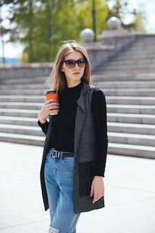 Mooi meisje permanent op straat met koffie en glazen.