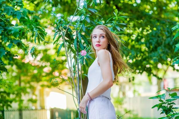 Mooi meisje poseren buiten, modieuze witte jurk dragen. zomerstijl.