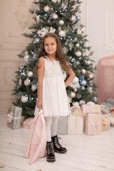 Mooi meisje poseren in de buurt van de kerstboom.