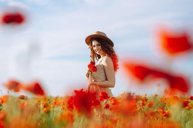 Mooi meisje poseren in een papaverveld