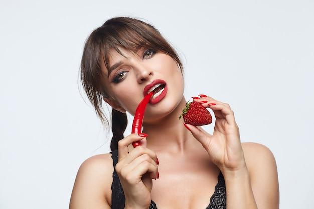 Mooi meisje poseren met rode chilipepers