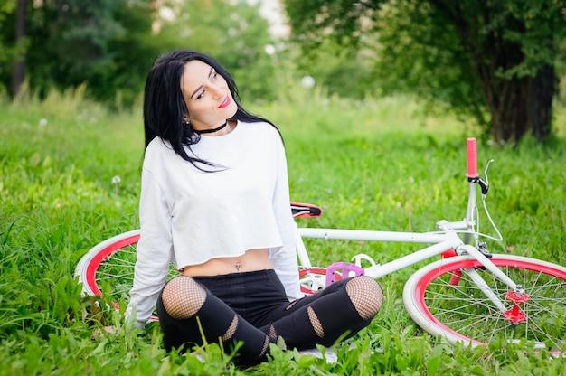 Mooi meisje poseren op een fiets. witte en rode fiets. wandelen in de natuur. gezonde levensstijl. weekend in de natuur portret van een gelukkig mooi meisje in een wit t-shirt. plek om te schrijven