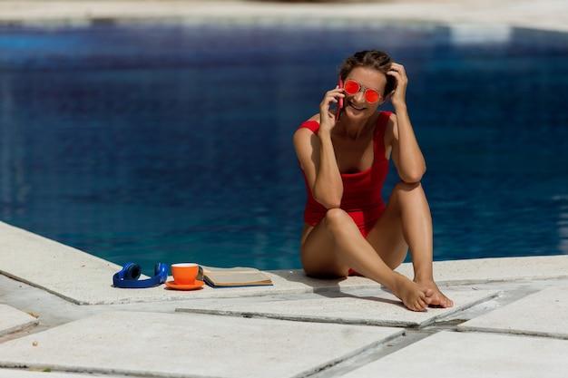 Mooi meisje praten aan de telefoon bij het zwembad