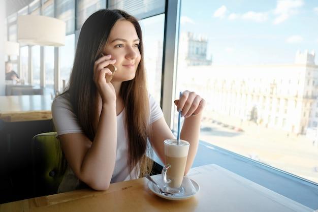 Mooi meisje praten in een café aan de telefoon met latte