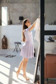 Mooi meisje probeert jurk in de kamer